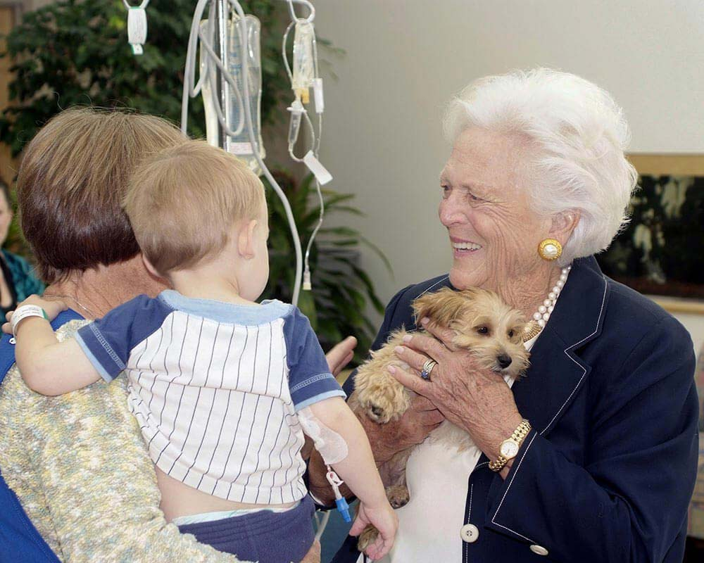 Mrs. Bush and her puppy greet a young patient