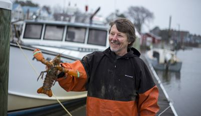 Lobsterman holding a lobster by ocean