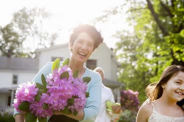 Woman and young girl with flowers outside of a house