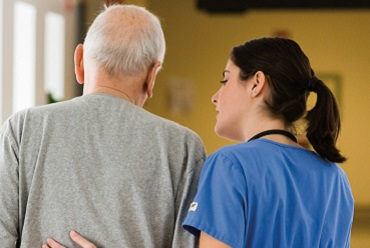 Healthcare provider helping an older man