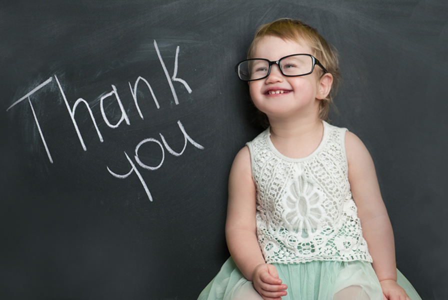 "Young girl sitting near the words ""Thank you"""