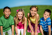 Group Of Kids Smiling In A Row Outdoors