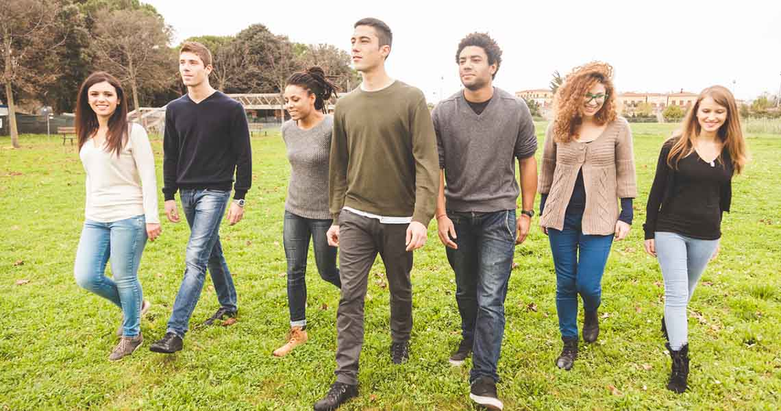Group of young adults walking together in a field