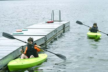 Two young boys in kayaks by a dock