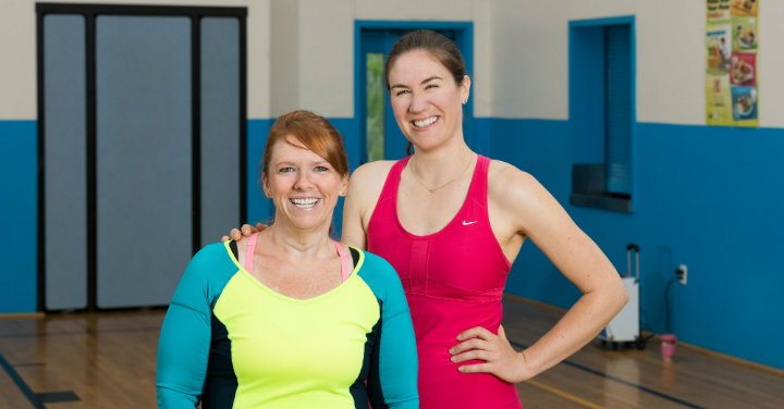 Two women in a gym smiling after a workout