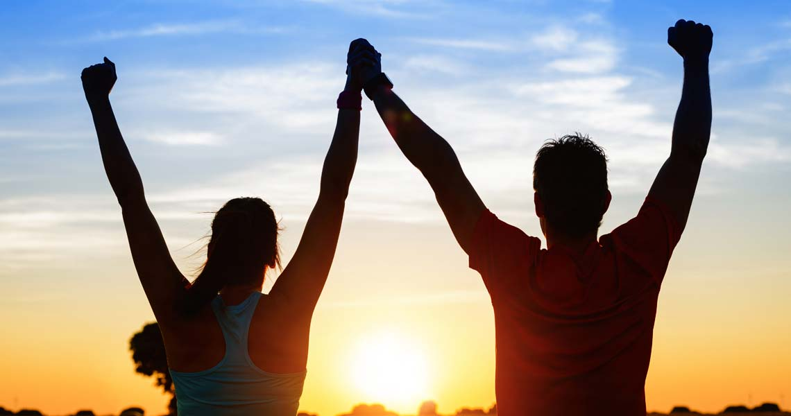 Couple raising arms towards the sun