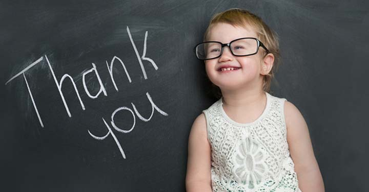 """Young girl wearing glasses in front of a blackboard that says """"Thank You"""""""