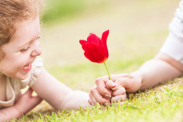 Young girl in the grass holding a bright red flower
