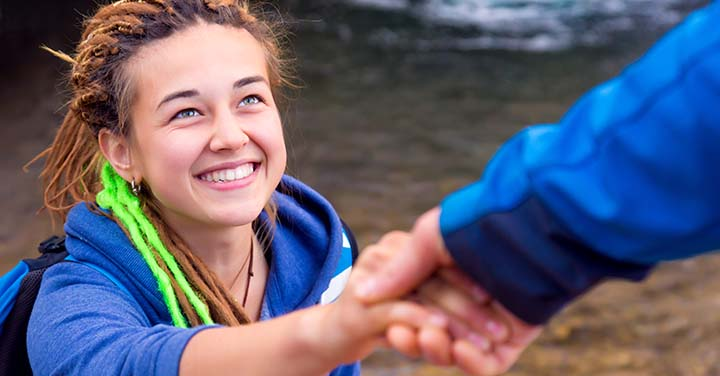 Young woman hiking next to a stream and holding the hand of someone else