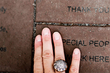 woman's hand placed atop bricks inscribed with kind sentiments