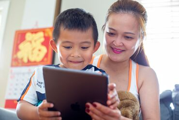 Lori Nguyen watches her 5 year old son, Billy Ha, play on an iPad
