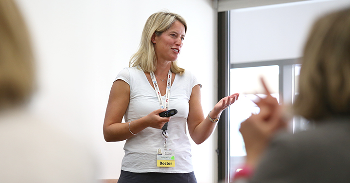 Woman presenting to group of adults