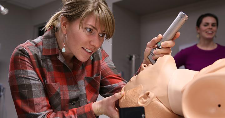 Woman intubating a training dummy