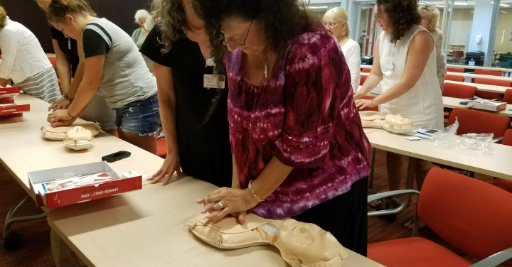 Woman practicing how to do Hands-Only CPR.