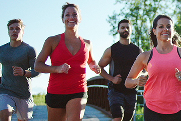 group of young adults running outside